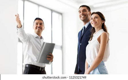 real estate business, sale and people concept - happy smiling realtor with folder showing customers new office room