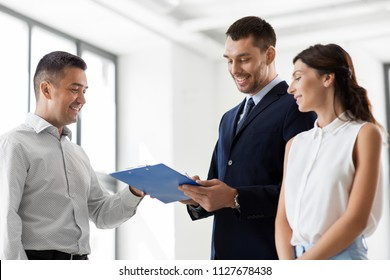real estate business, sale and people concept - male realtor with clipboard and pen showing contract document to customers at new office room