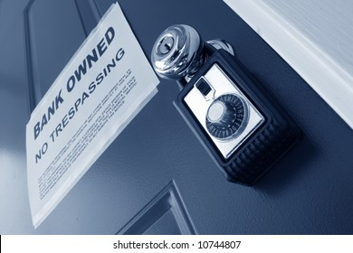 Real estate combination lock box on foreclosed house door with bank owned lender foreclosure notice (fictitious document with authentic legal language)