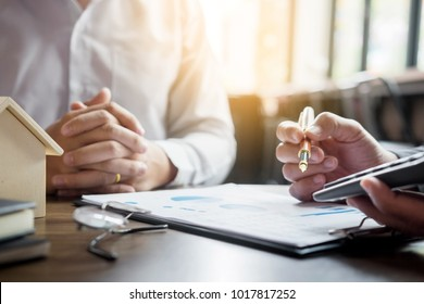 Real Estate concept, Agent holds calculator for present price for loan investment chart graph documents and calculating table payment to customer