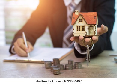 Real estate concept - business man signs contract behind house architectural model