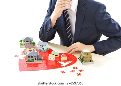 Real estate concept - business man and house architectural model