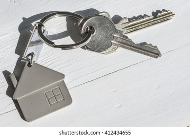 Real estate concept. Close up of keys on white wooden sunny background.