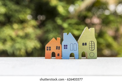 Real estate concept, design wooden house over blurred natural bokeh background