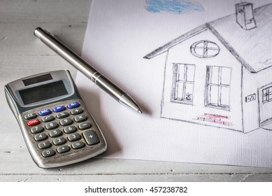 Real estate concept. A drawing of a house, pencil and calculator.