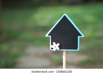 Real estate concept: finding or selling property with a stand that shapes like a house in a garden
