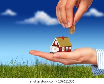 Real estate concept. Hand with coin and house.