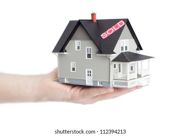 Real estate concept - hand holding household architectural model, isolated