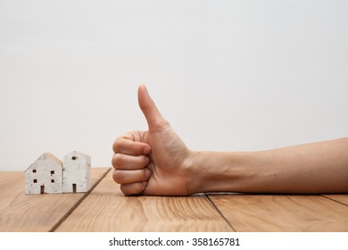 Real estate concept a hand showing thumb up at miniature house