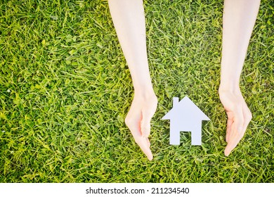 Real estate concept - hands of a young woman surround a white cutout house over green grass, copy space available.
