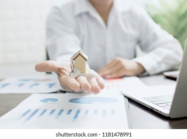 Real estate concept, home agent holding house, banker showing model on fiance graph and working table in bank