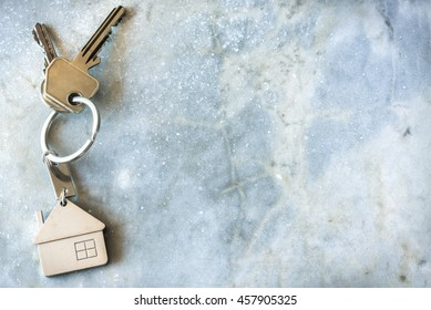 Real estate concept. Home keys on a marble background. Space for copy.
