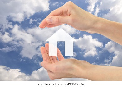 Real estate concept. Icon of an apartment house in human hands against the sky
