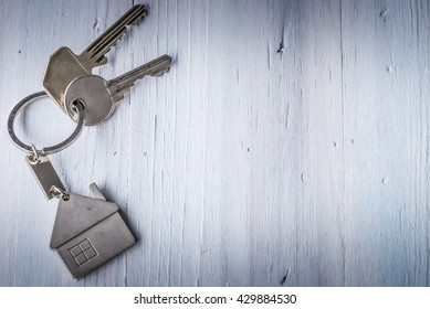Real estate concept - Key ring and keys on white wooden background - Low key light