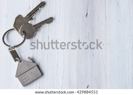 Real estate concept - Key ring and keys on white wooden background - Copy space