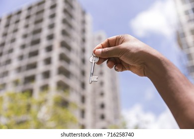 Real estate concept. Male Hand holding a key on blurred background