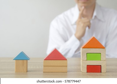 Real estate concept - man making  decision to choose the house behind home  model.