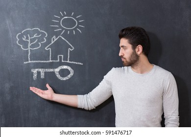 Real Estate Concept. Portrait of man in front of chalkboard with house key