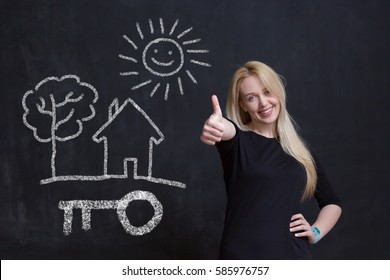 Real Estate Concept. Portrait of woman in front of chalkboard with house key