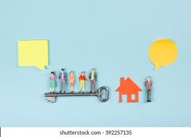 Real Estate concept. Speech bubbles and people toy figures Construction, building. Paper model house with key on blue background. Top view. Copy space for text.