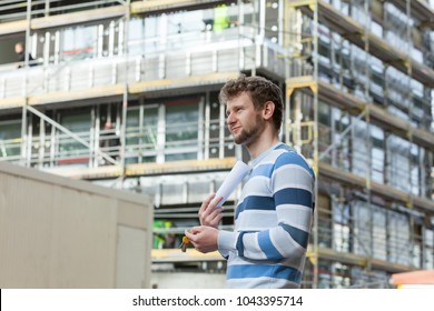 Real estate concept - young man on front of new big modern house building construction site with keys and blueprint project