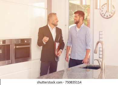 Real estate consultant talking about house while inspecting the kitchen with smiling customer