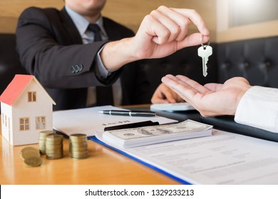 Real Estate developer Agent and sign on document giving keys of new house, Property agent giving offer to buyer