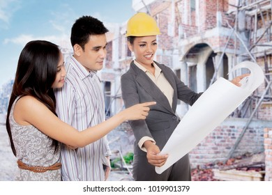 Real estate developer showing a blue print to new house buyer