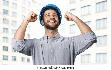 Real estate development - happy excited engineer celebrating success in front of new building.