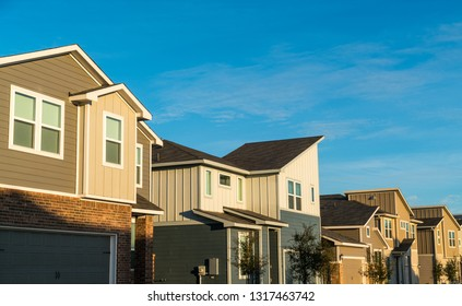 Real estate development homes and houses with modern design and angled roofs looking up at houses with perfect sunshine and blue sky