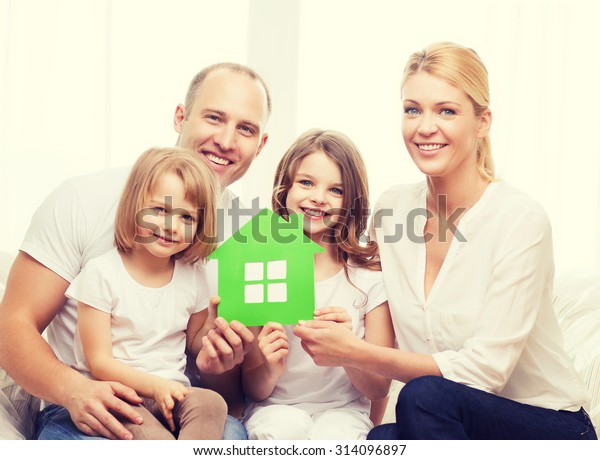real estate, family, children and home concept - smiling parents and two little girls holding green house