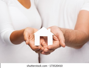 real estate and family concept - closeup of couple hands holding paper house