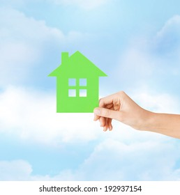 real estate and family home concept - closeup picture of female hand holding green paper house