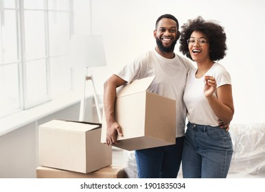 Real Estate And Family Housing. African American Couple Posing With Moving Boxes And New House Key Hugging Smiling To Camera Standing Indoors. Empty Space For Text
