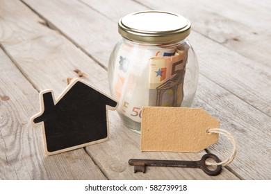 Real estate finance concept - money glass with vintage key and little house