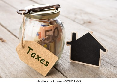 Real estate finance concept - money glass with Taxes word and vintage key