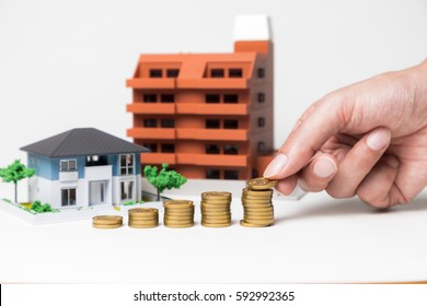 real estate and funds, hand holding a coin