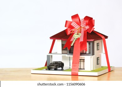 Real estate and Gift new home concept,Model house with Red ribbon and key on white background