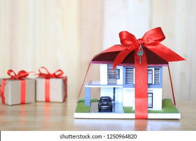 Real estate and Gift new home concept,Model house with Red ribbon and key on wooder background