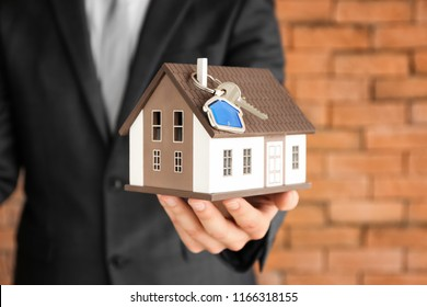 Real estate with house model and key, closeup