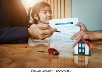 real estate Insurance concept, Parent signing at agreement document for insure house and car with his daughter.