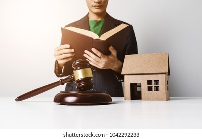 Real estate insurance lawyer working hard job, signing a contract with wooden house model.