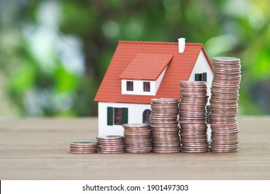 Real estate investment concept composed of rising dollar coins and small house model