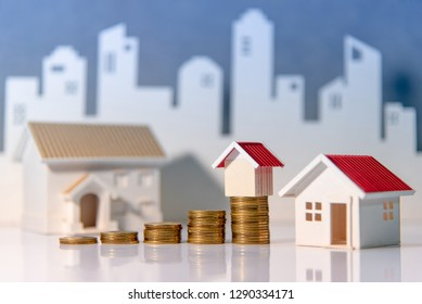Real estate investment or Home mortgage loan rate. Property ladder concept. Coins stack and house models on the table with white city background. Money investing and business growth.