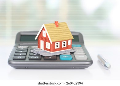 Real estate investment. House and calculator on table.