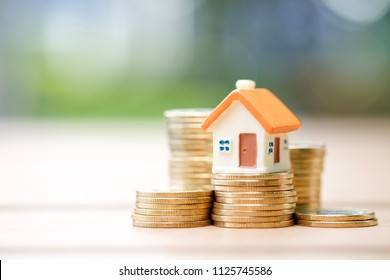 Real estate investment. House model standing on a heap of coins.