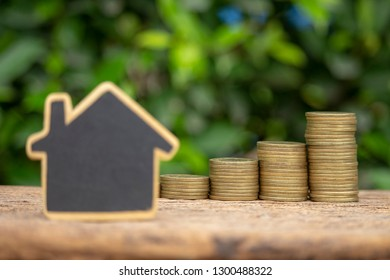 real estate investment,image of stack coins with blur house model select focus at coins.