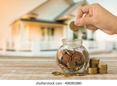 real estate investment,property investment, plan for housing concept. hand putting coin in money jar.