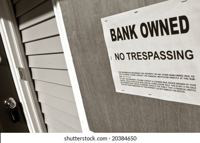 Real estate lender bank owned no trespassing sign notice posted on the boarded up window of a vacant house in repossession foreclosure (fictitious document with authentic legal language)