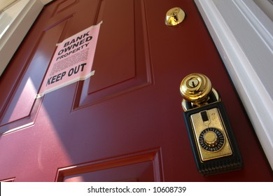 Real estate lock box and bank owned keep out bank owned financial lender foreclosure notice on a house door (fictitious document with authentic legal language)